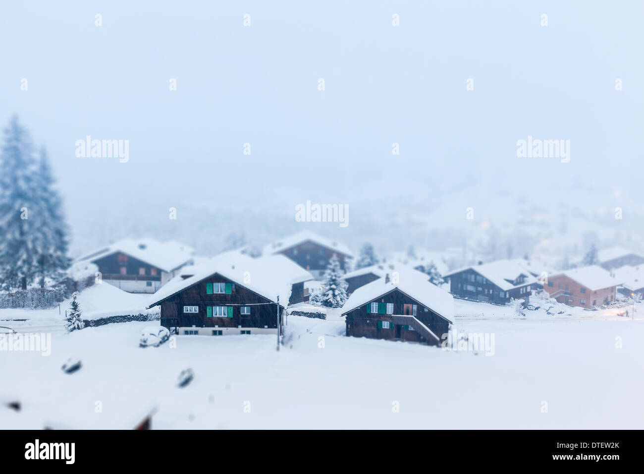 Traditional wooden houses in Grindelwald, Switzerland during heavy snow fall. - Stock Image