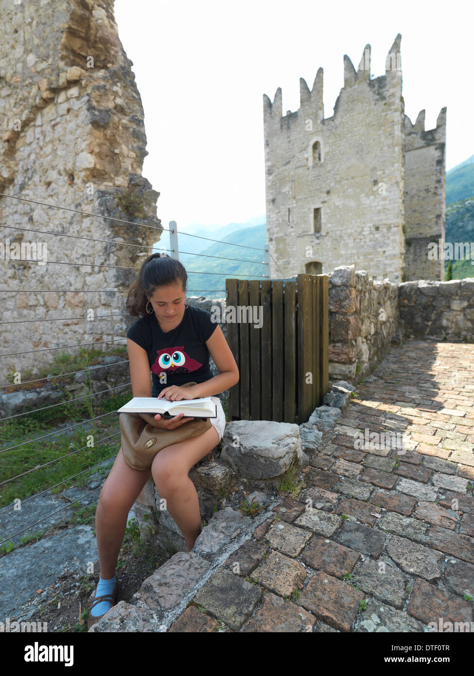 Arco, Italy, 15 years young on Castello di Arco reading Stock Photo