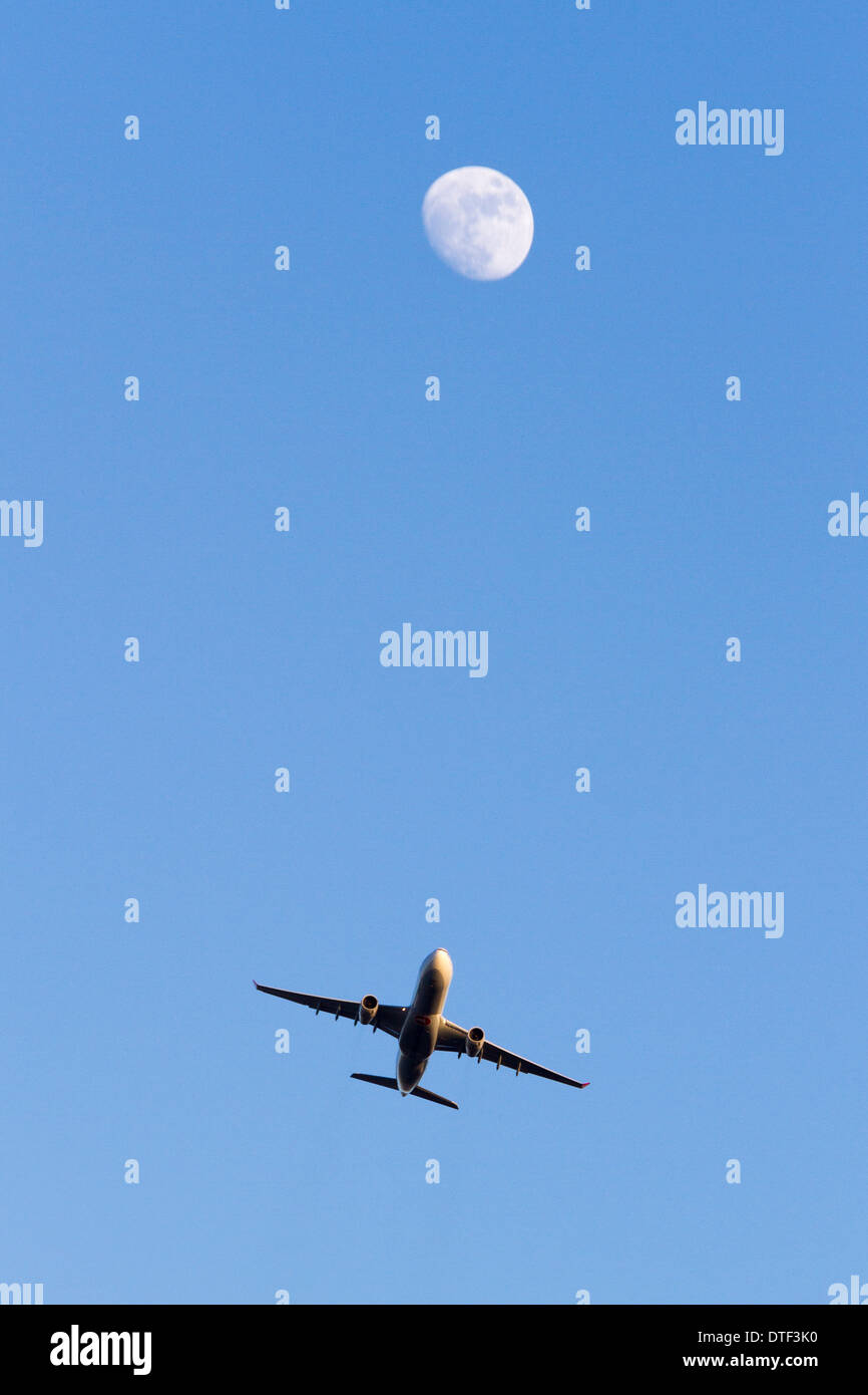 Plane flying across the sky with the moon in the background, England, UK - Stock Image