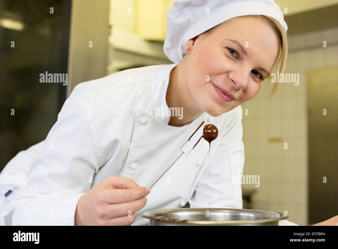confectioner producing filled chocolates in confectionery - Stock Image