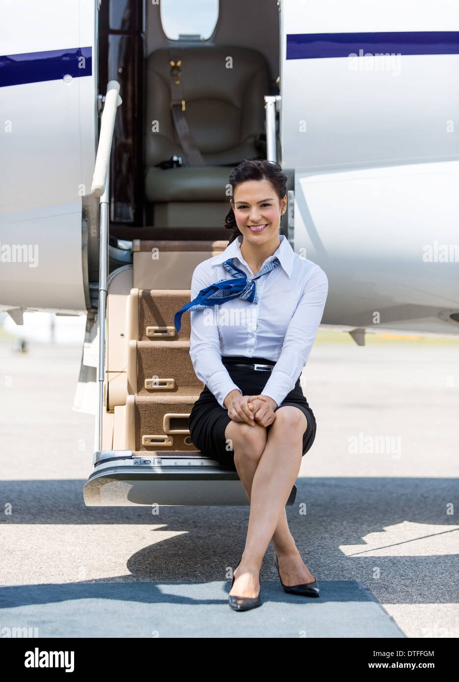 Air Hostess Sitting On Ladder Of Private Jet - Stock Image
