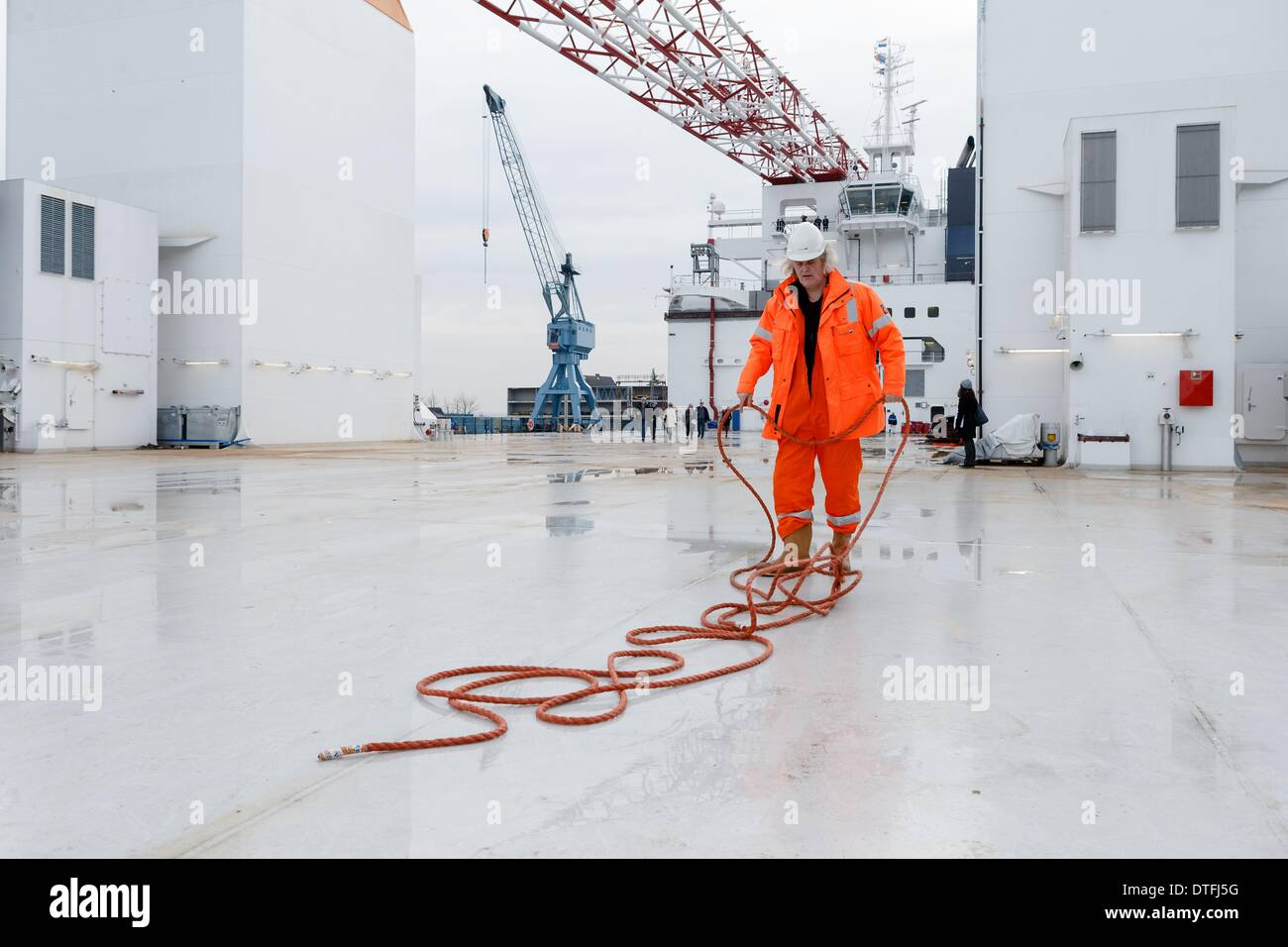 Hamburg, Germany. 17th Feb, 2014. A crew member disentangles a rope on the deck of wind turbine installation vessel Aeolus at the Sietas shipyard in Hamburg, Germany, 17 February 2014. Aeolus is the first wind turbine installation vessel to be designed and built in Germany and will be used by Van Oord for the construction of wind turbines at the Eneco Luchterduinen wind park from July 2014. Photo: MARKUS SCHOLZ/DPA/Alamy Live News - Stock Image