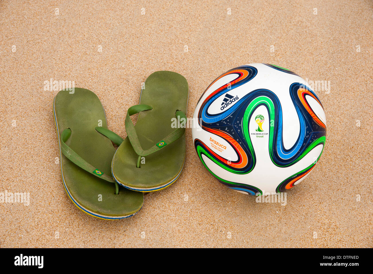 Brazuca (replica), official match ball of the FIFA World Cup 2014 in Brazil in the sand next to worn out green flip-flops - Stock Image