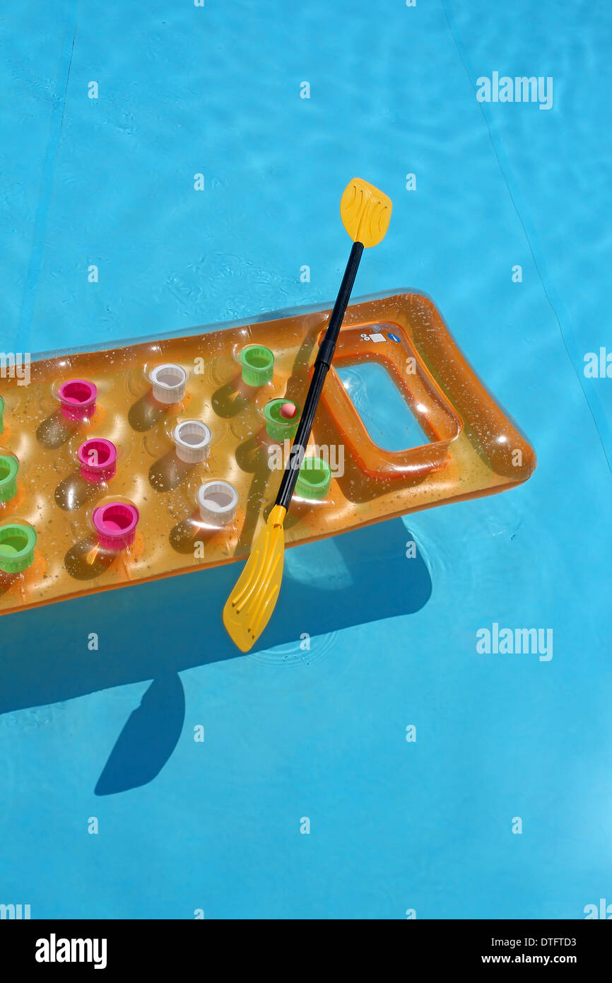 Yellow air mattress with oar in swimming pool - Stock Image