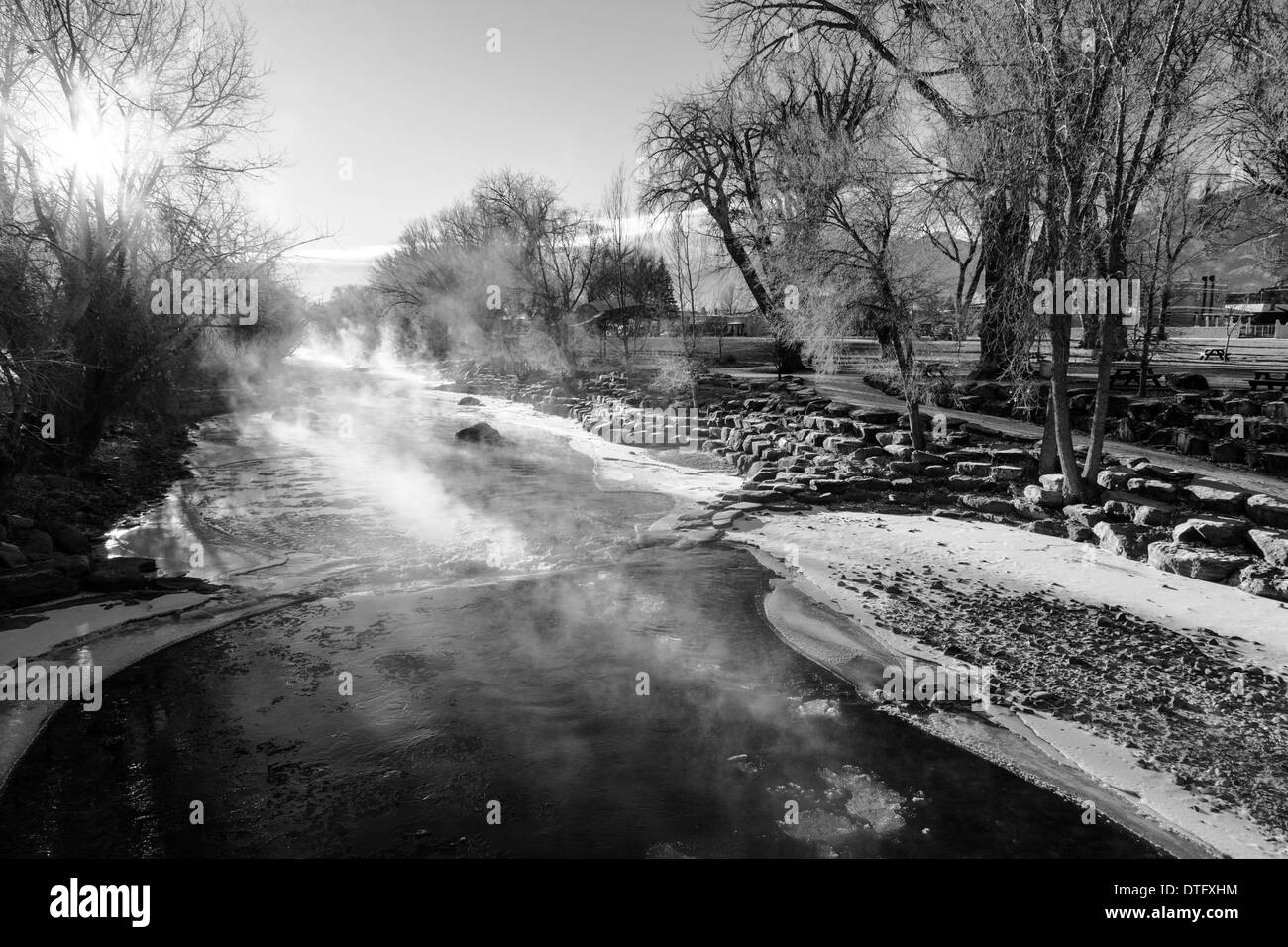 Black & white view of steam rising on a sub-zero morning from snow and ice choked Arkansas River, which runs through Salida, CO - Stock Image