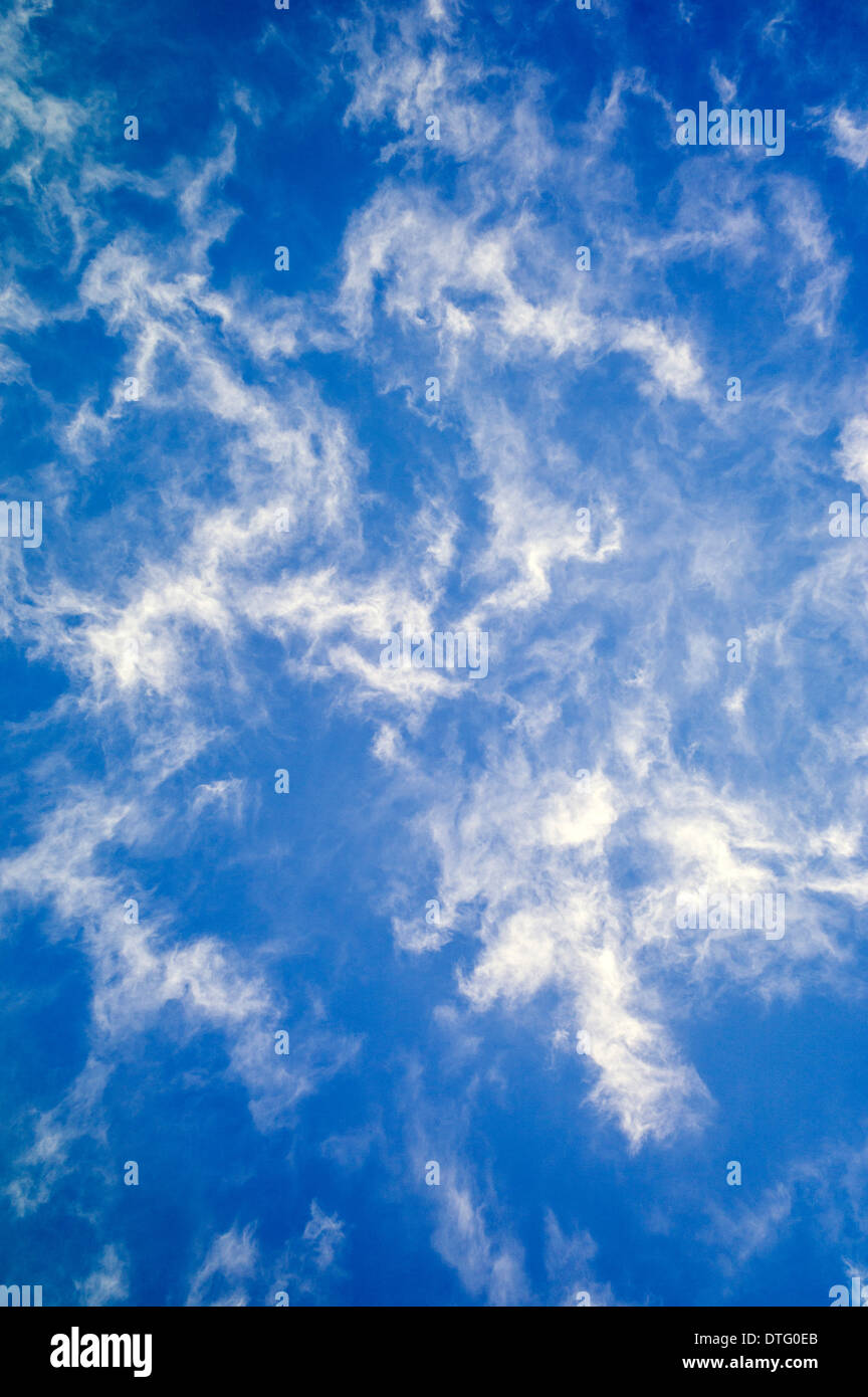 Wispy white clouds against a cobalt blue sky - Stock Image
