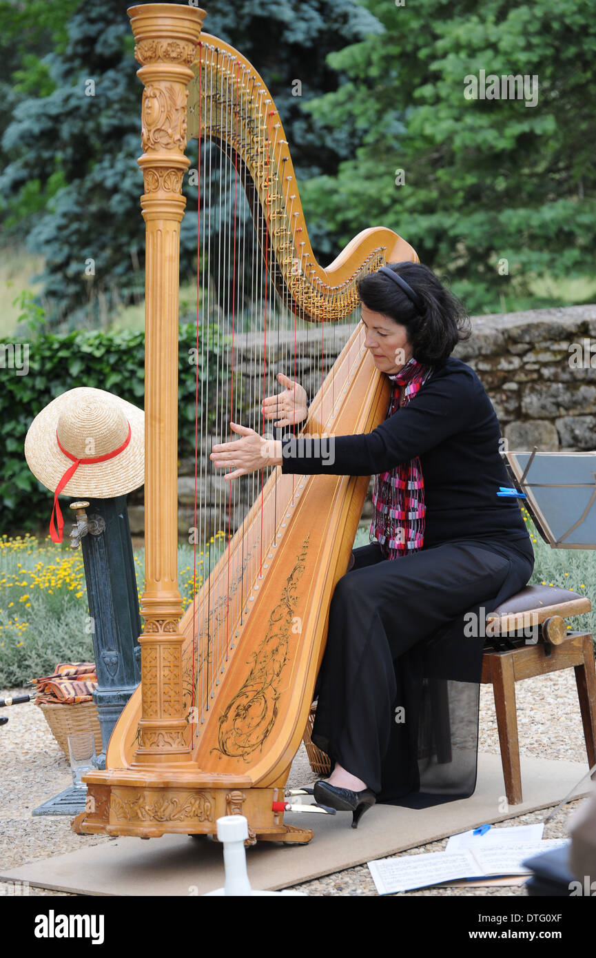 Lady musician playing harp in France - Stock Image