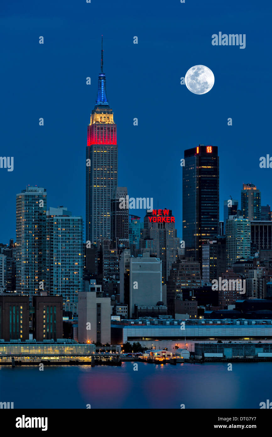 The full moon rises over the New York City (NYC) skyline during the twilight hour. A view from New Jersey across the Hudson River with The Empire State Building illuminated in red, white and blue. - Stock Image