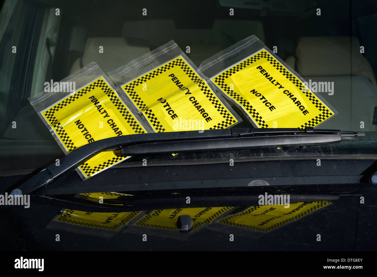 Three parking tickets on car window. - Stock Image