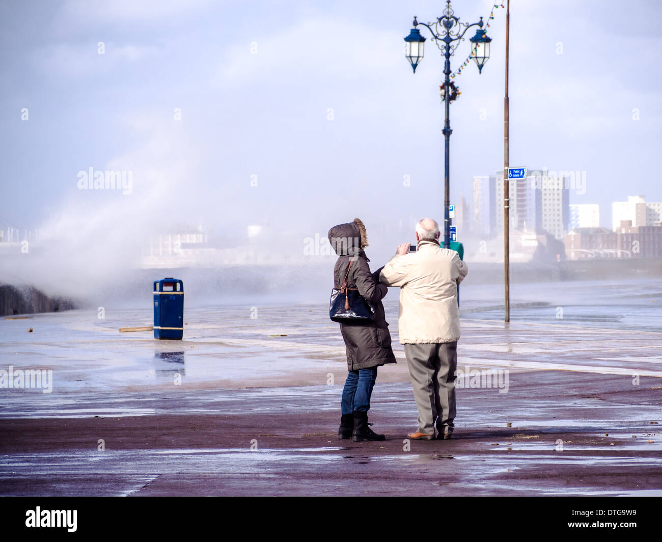 A senior man and lady taking photographs of waves on Southsea seafront, Portsmouth, Engalnd Stock Photo