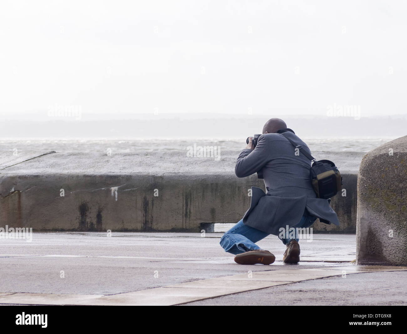 A photographer taking photographs of waves on southsea seafront, England - Stock Image