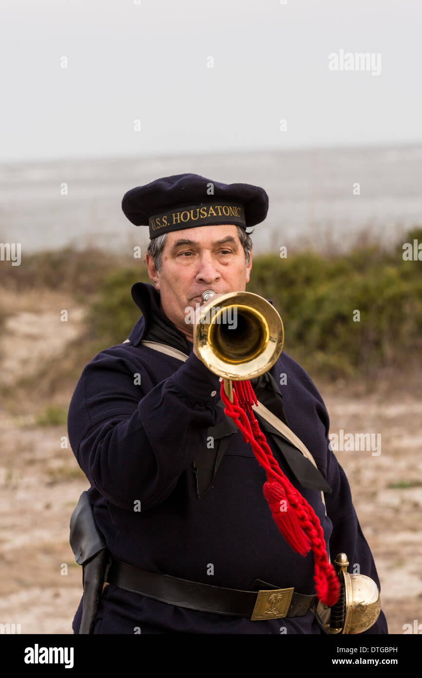 A lone bugler plays taps along Breach Inlet in honor of the sailors of the Union navy ship the USS Housatonic sunk by the Confederate submarine H.L. Hunley 150-year-ago during the Civil War February 17, 2014 on Sullivan's Island, SC. The Hunley was the first submarine to sink a ship in battle and then suffered an accident killing the crew. - Stock Image