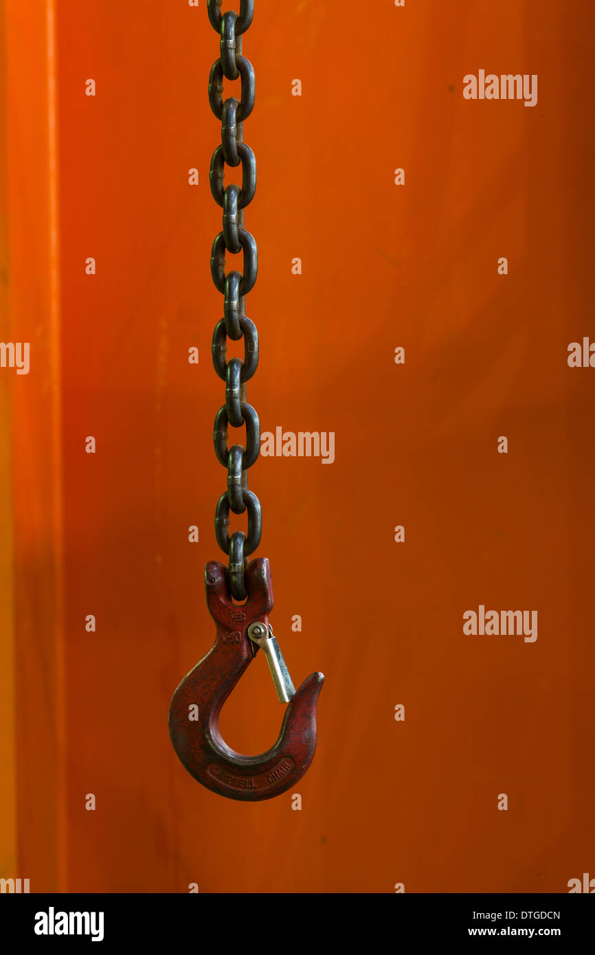 Abstract image of a small crane hook against a red pillar - Stock Image