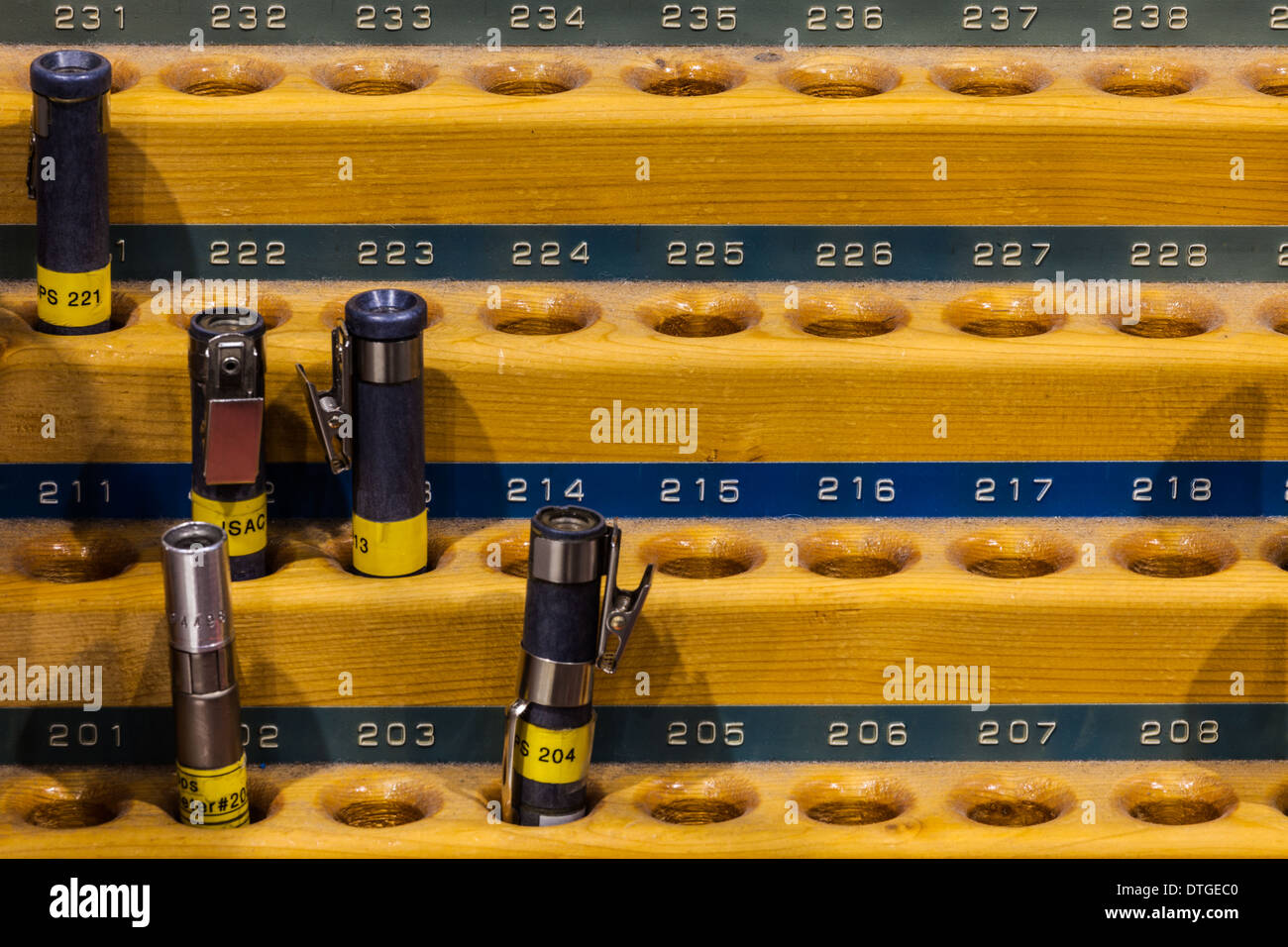 Pencil style radiation dosimeters in a wooden rack - Stock Image