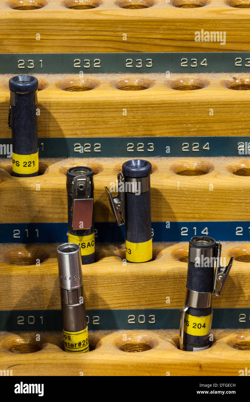 Five pencil style radiation dosimeters in a rack - Stock Image