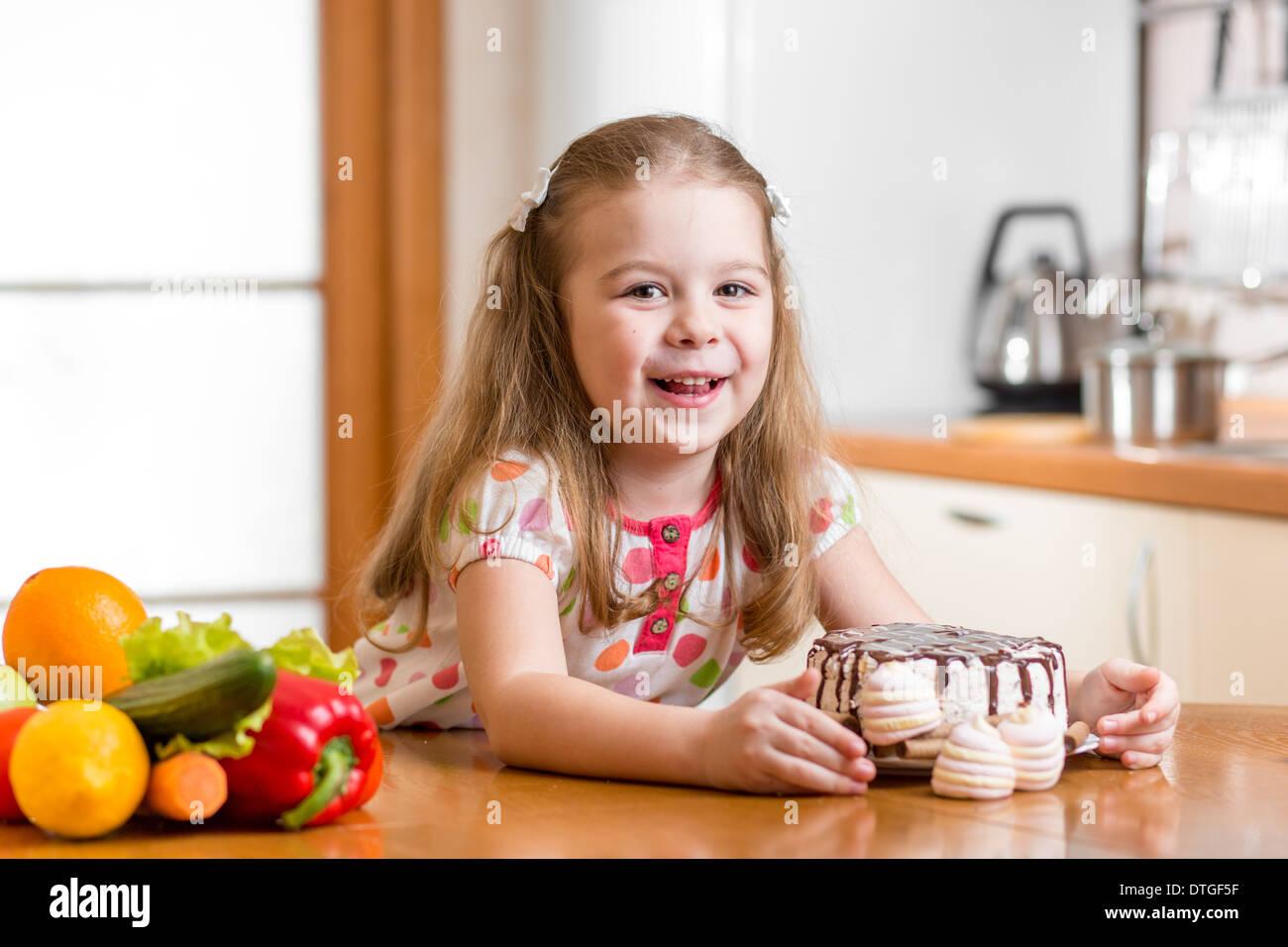 kid choosing between healthy vegetables and tasty sweets - Stock Image
