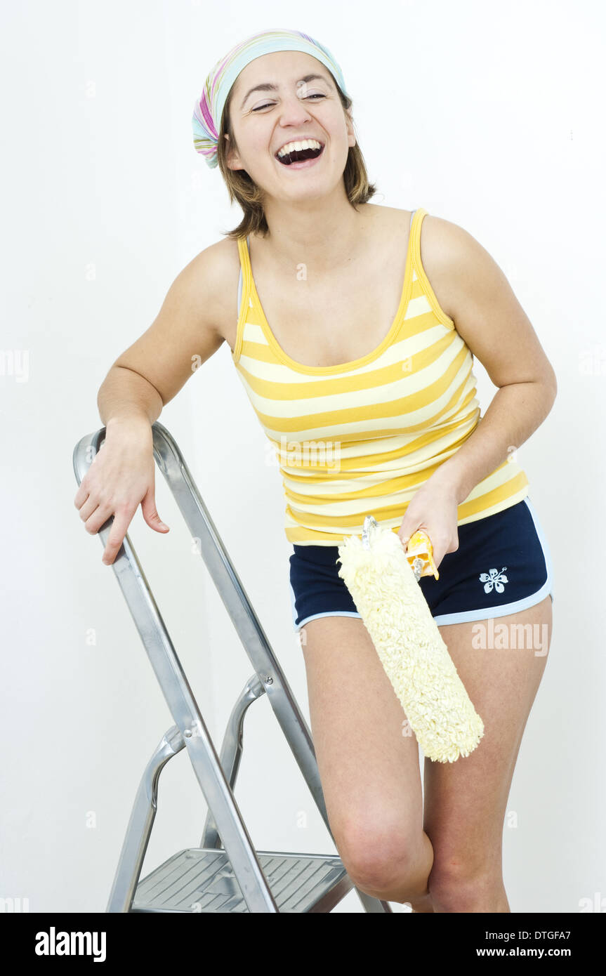 young woman on the ladder laughing cheerfully with a painting roller in her hand (model-released) - Stock Image