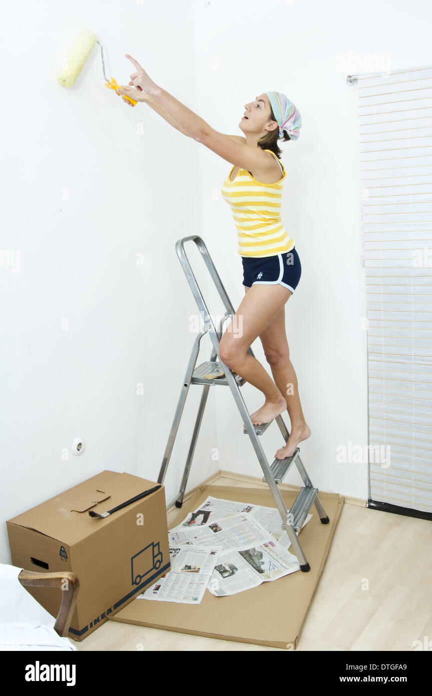 Young Woman On The Ladder Painting The Wall Model Released Stock
