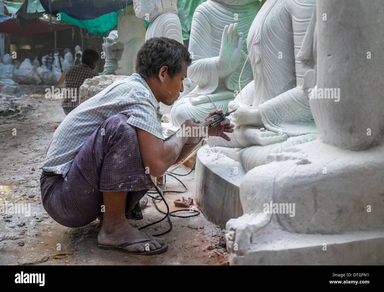 Young man carving an image of Buddha marble in a workshop in Mandalay, Myanmar Stock Photo