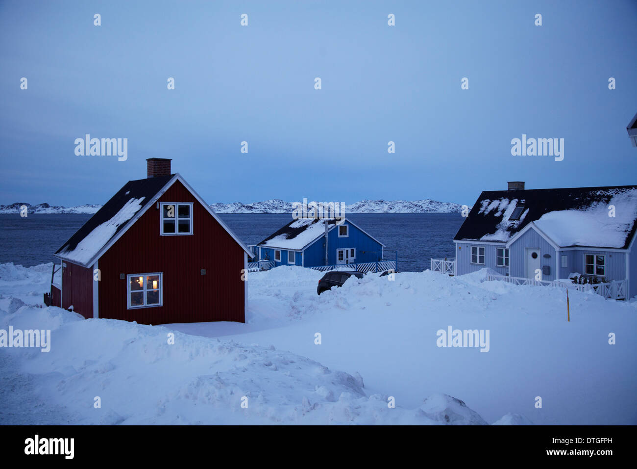 Houses in Nuuk city, Greenland and the fjord in the background. The blue hour. The sun has left and the darkness taking over. - Stock Image