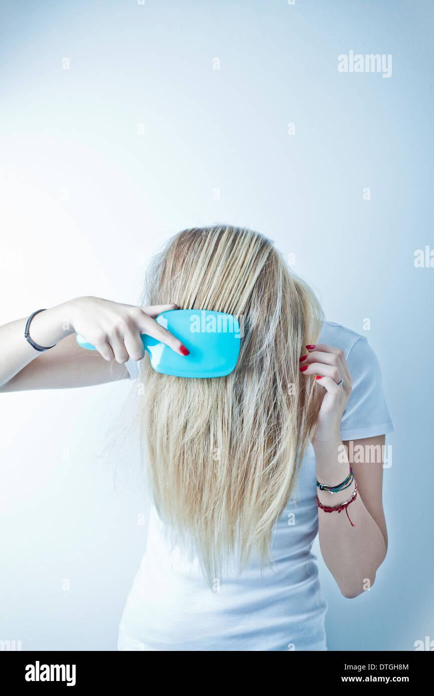 teenage girl brushing the hair - Stock Image