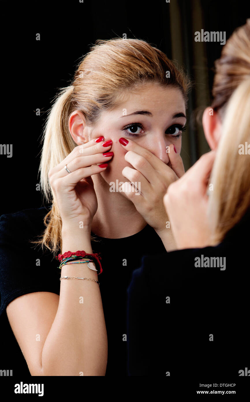 teenage girl squeezing a pimple - Stock Image
