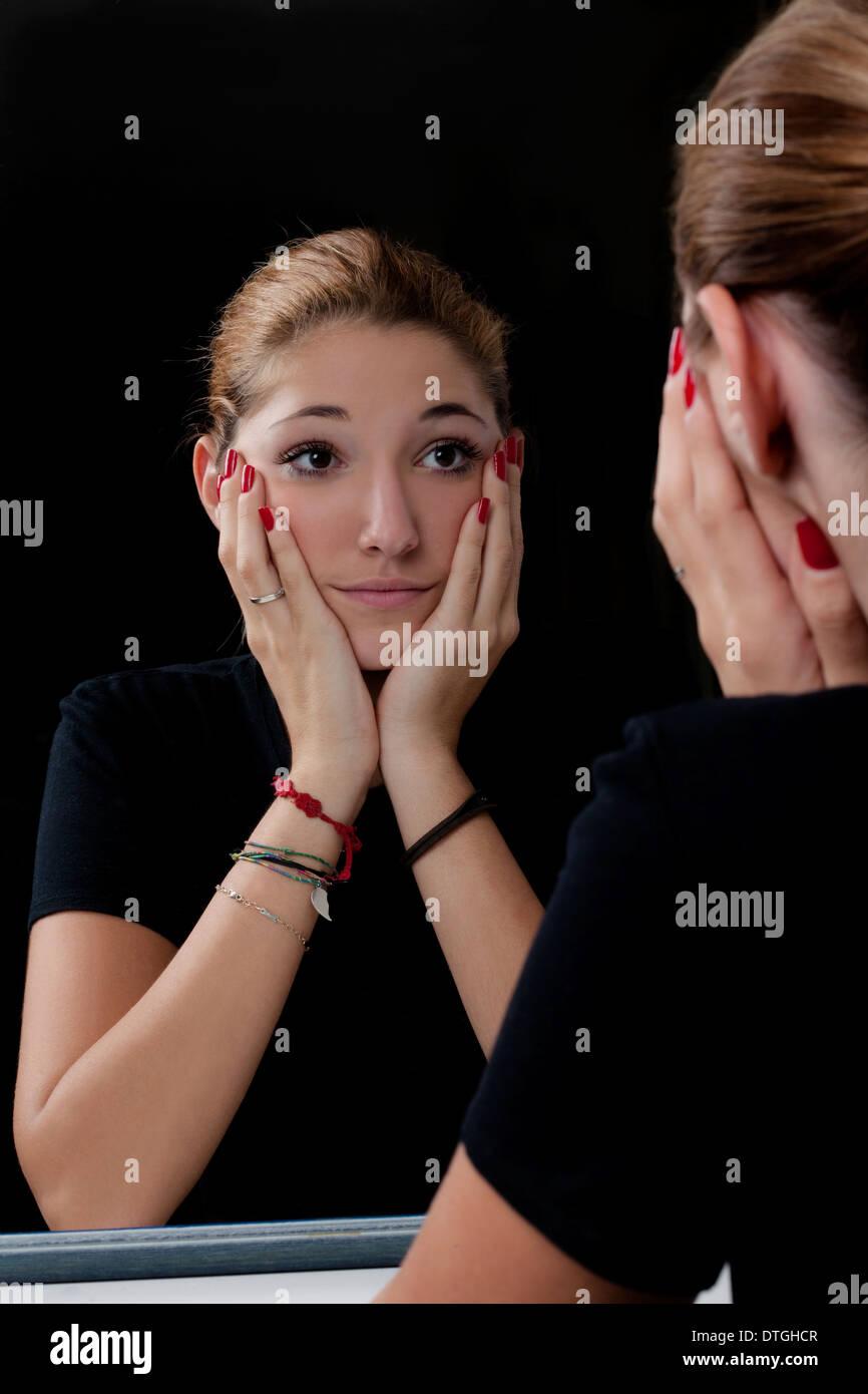 ragazza si guarda allo specchio - Stock Image
