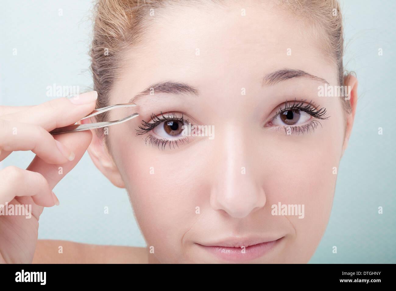 teenage girl shaving eyebrows - Stock Image