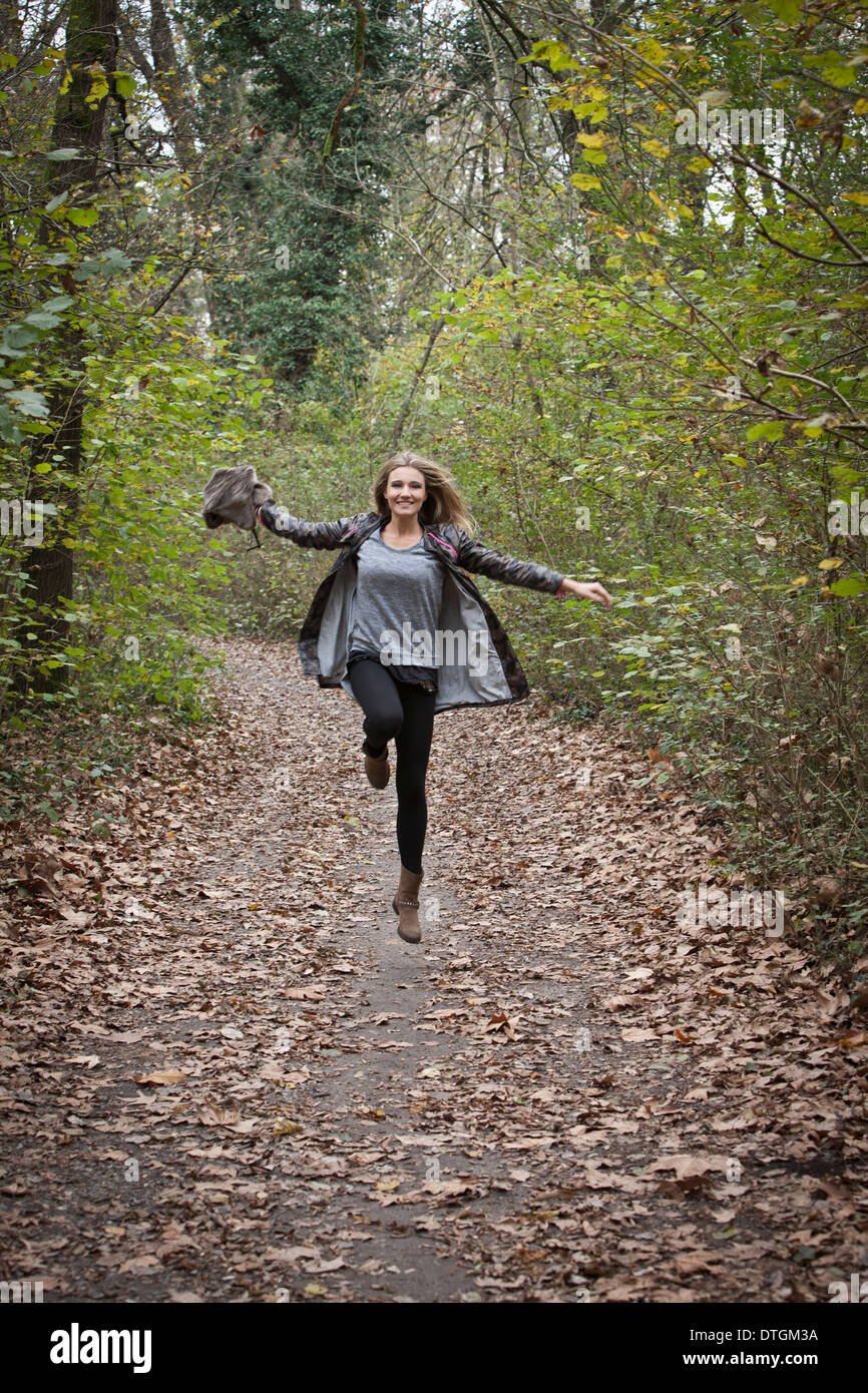 woman jumping in forest - Stock Image