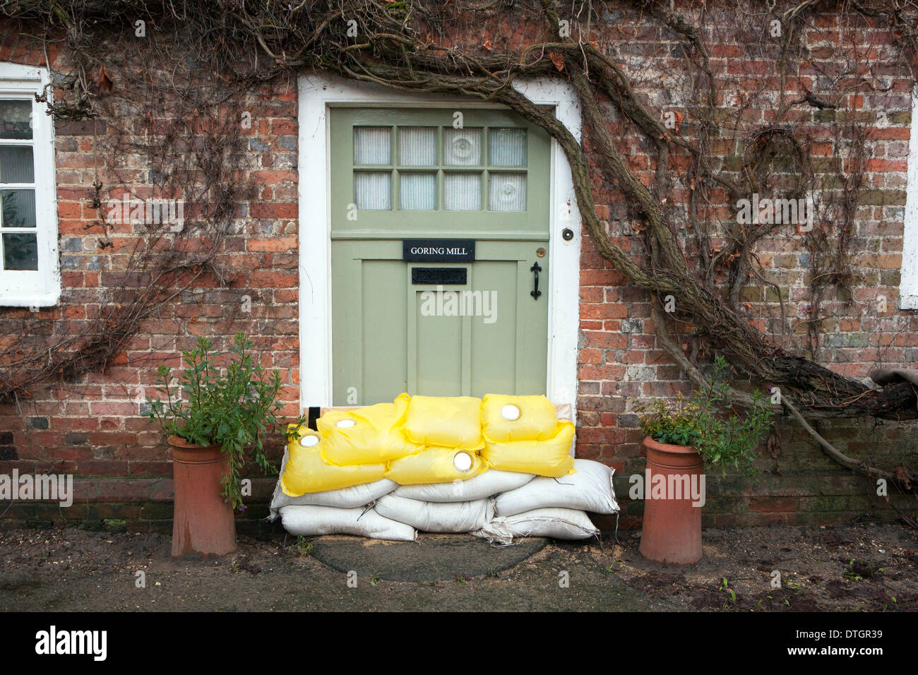 A sage green front door with sand bags, flood protection. Stock Photo