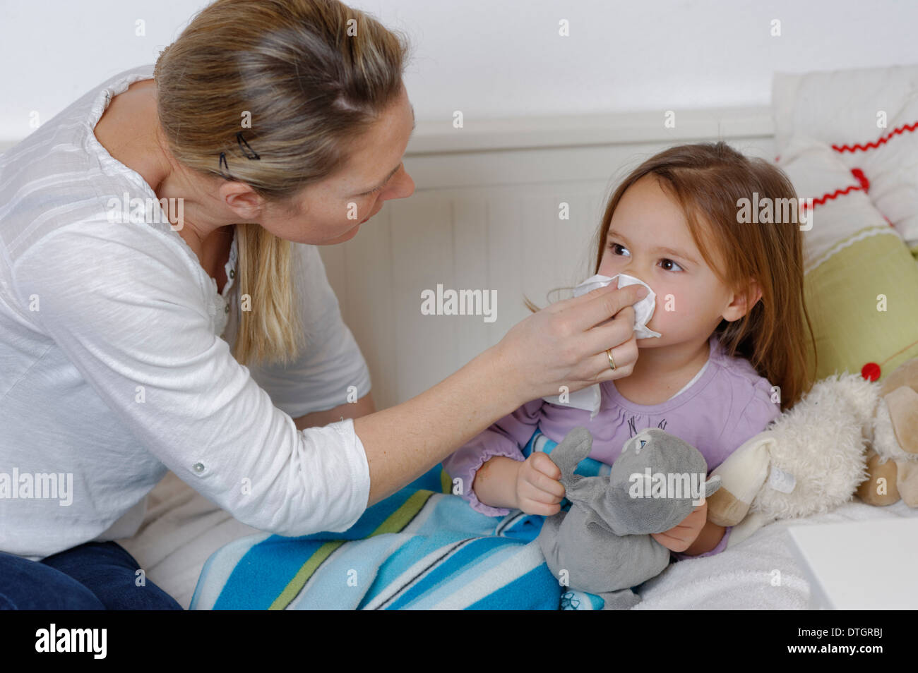 Mother taking care of her sick daughter, wiping the girl's nose, girl lying in bed - Stock Image