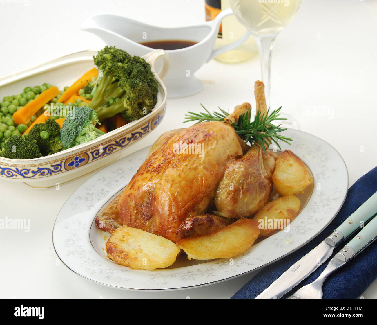 SUNDAY ROAST. Oven roast chicken with golden roast potatoes, mixed vegetables, gravy and a glass of white wine - Stock Image