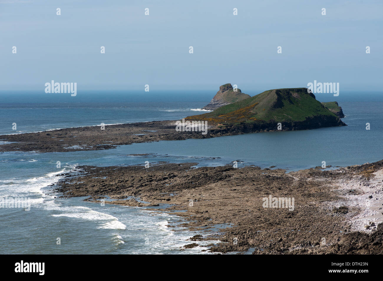 at half tide the water rushes over the causeway between the Worms head and the shore creating an island - Stock Image