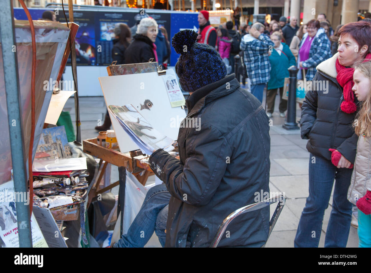 An artist paints at her stall in the German Christmas Market in Bath ...