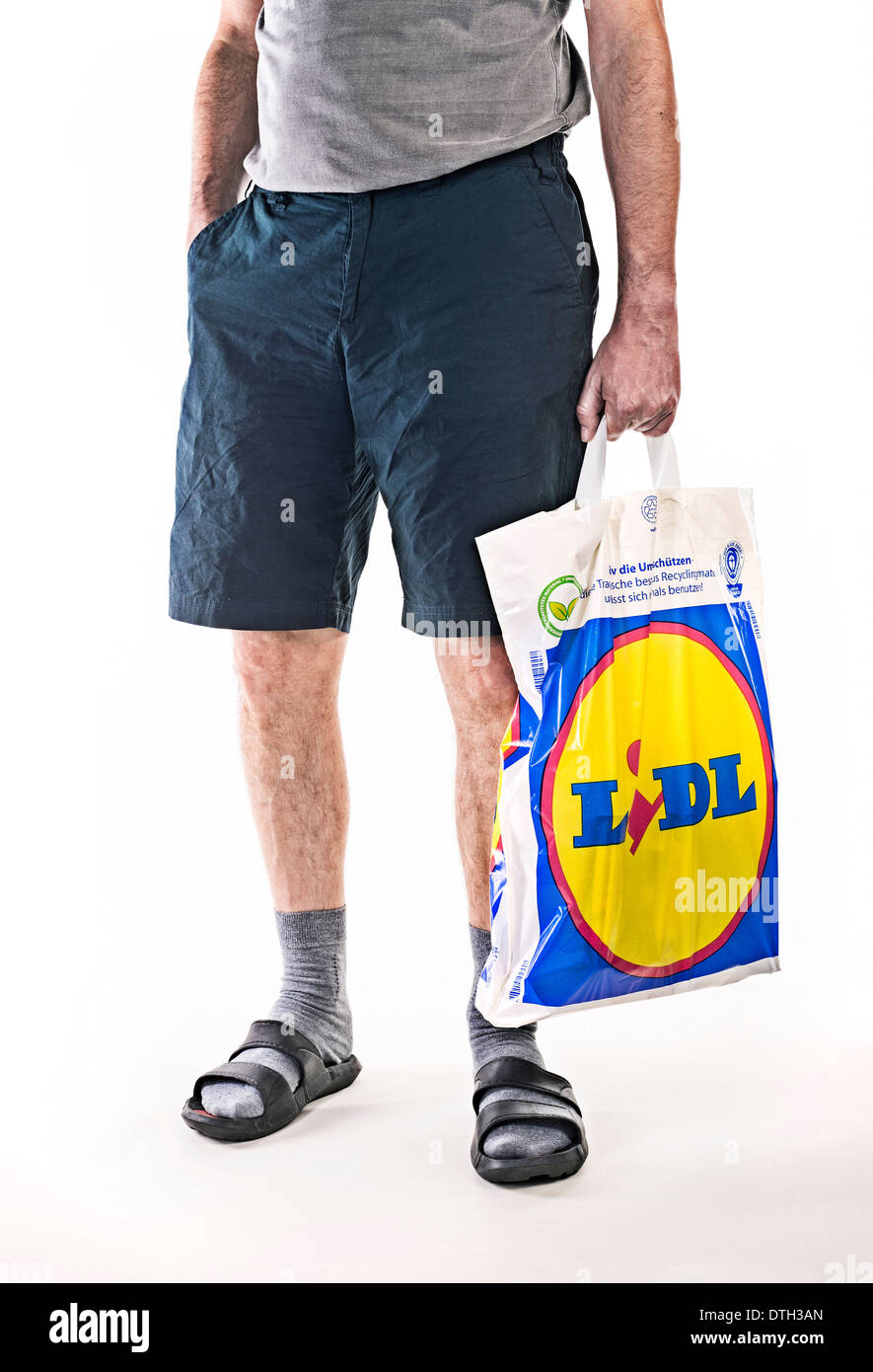 Lower body of a man with short pants, carrying a plastic bag of food discounter Lidl. Stock Photo