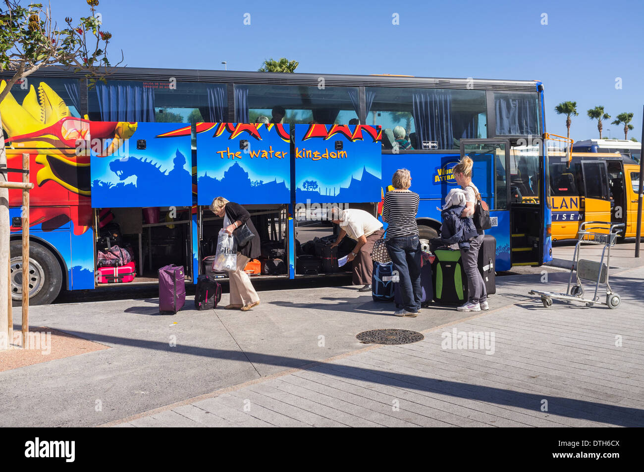 Passengers loading cases on to a Siam Park coach at Tenerife Sur airport arrivals for transfer to their resort, Canary Islands, - Stock Image