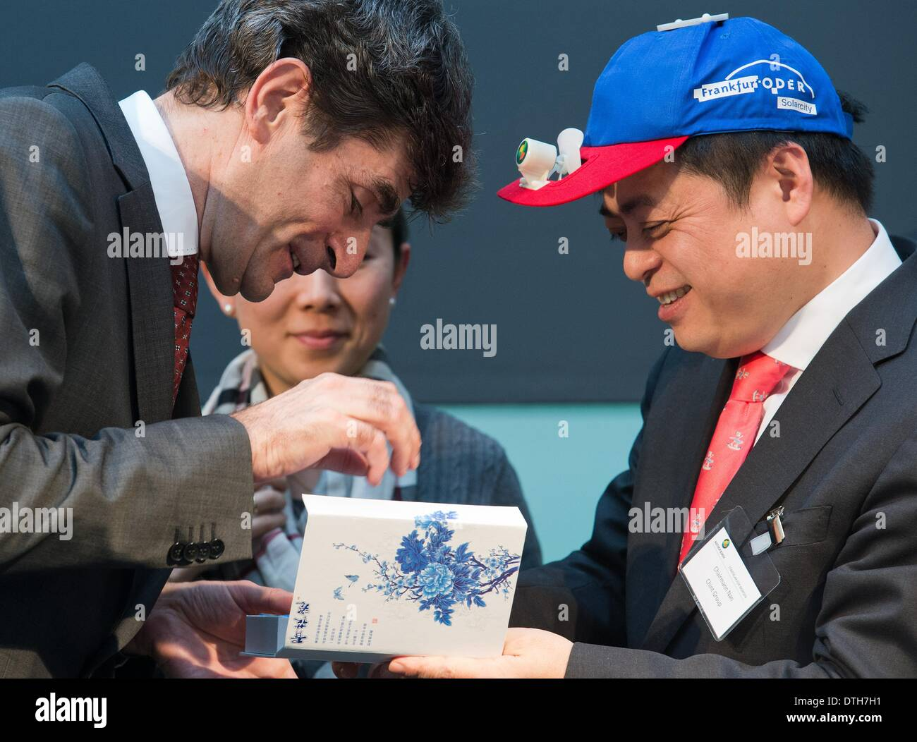 Frankfurt Oder, Germany. 18th Feb, 2014. Chint Group Manager Cunhui Nan (r) and mayor Martin Wilke (non-party) exchange presents at the opening of the solar plant of the Astronergy Solarmodule GmbH company in Frankfurt Oder, Germany, 18 February 2014. The Astronergy Solarmodule GmbH took over the module factory of insolvent solar company Conergy in early 2014. Astronergy is part of the worldwide operating Chint Group. Photo: Patrick Pleul/ZB/dpa/Alamy Live News - Stock Image