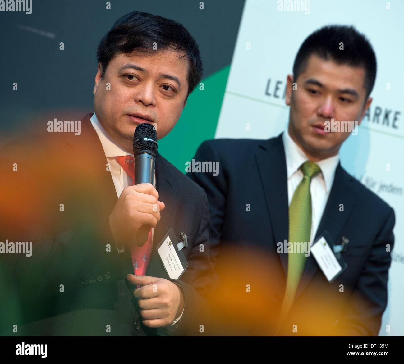 Chint Group Manager Cunhui Nan (L) speaks at the opening of the solar plant of the Astronergy Solarmodule GmbH company in Frankfurt Oder, Germany, 18 February 2014. Vice President of the Chint Group Chuan Lu is pictured behind Nan. The new Chinese owner presented his plans for the plant on the same day. The Astronergy Solarmodule GmbH took over the module factory of insolvent solar company Conergy in early 2014. About 200 jobs are supposed to be saved at the location. Astronergy is part of the worldwide operating Chint Group. Photo: Patrick Pleul/ZB - Stock Image