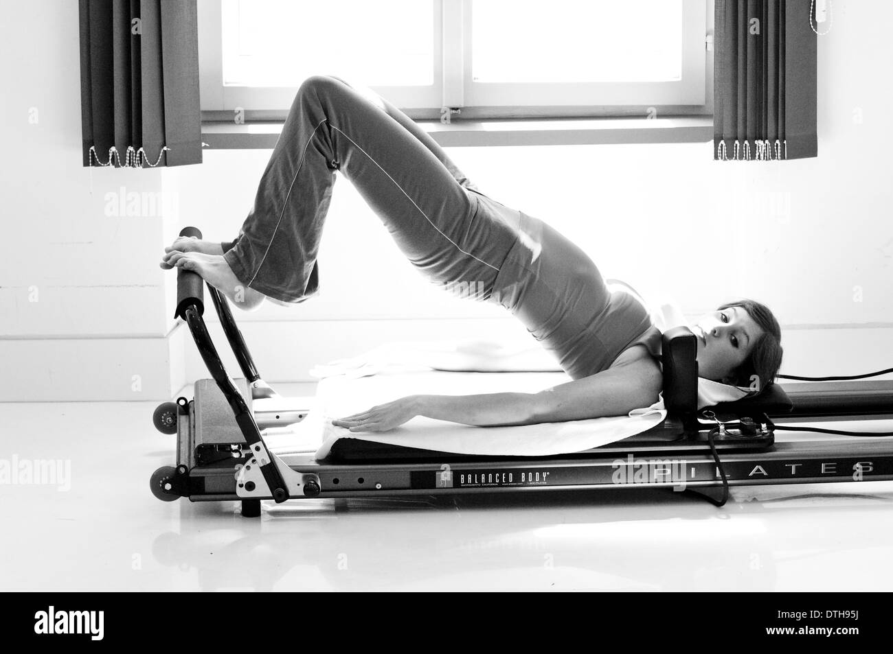 young woman in fitness studio on the pilates trainer Austria (model-released) - Stock Image