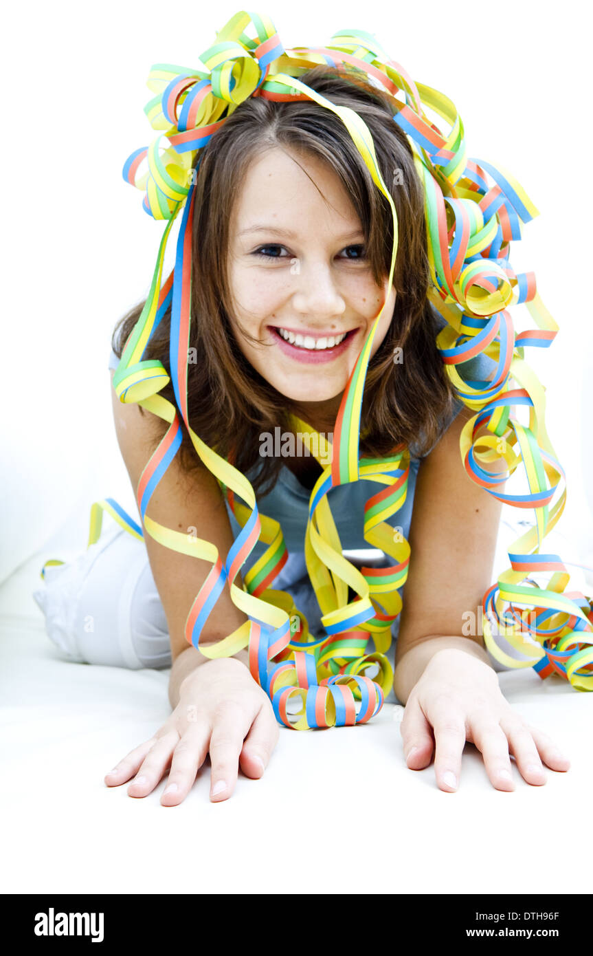 Young woman in the midst of paper streamers (model-released) - Stock Image