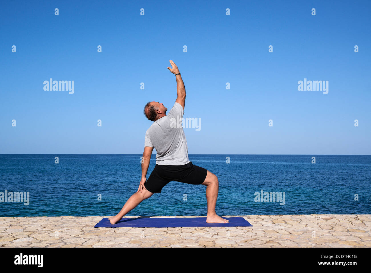 Man practice yoga meditation from an ocean waterfront ledge, Negril, Jamaica. - Stock Image