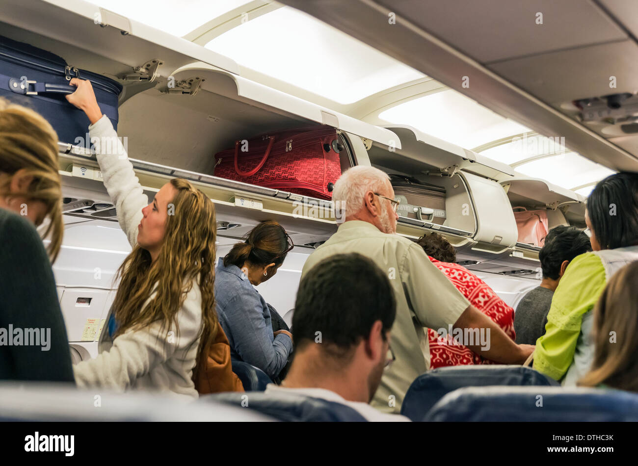 Airline travelers retieve their carry-on luggage from overhead compartments. - Stock Image