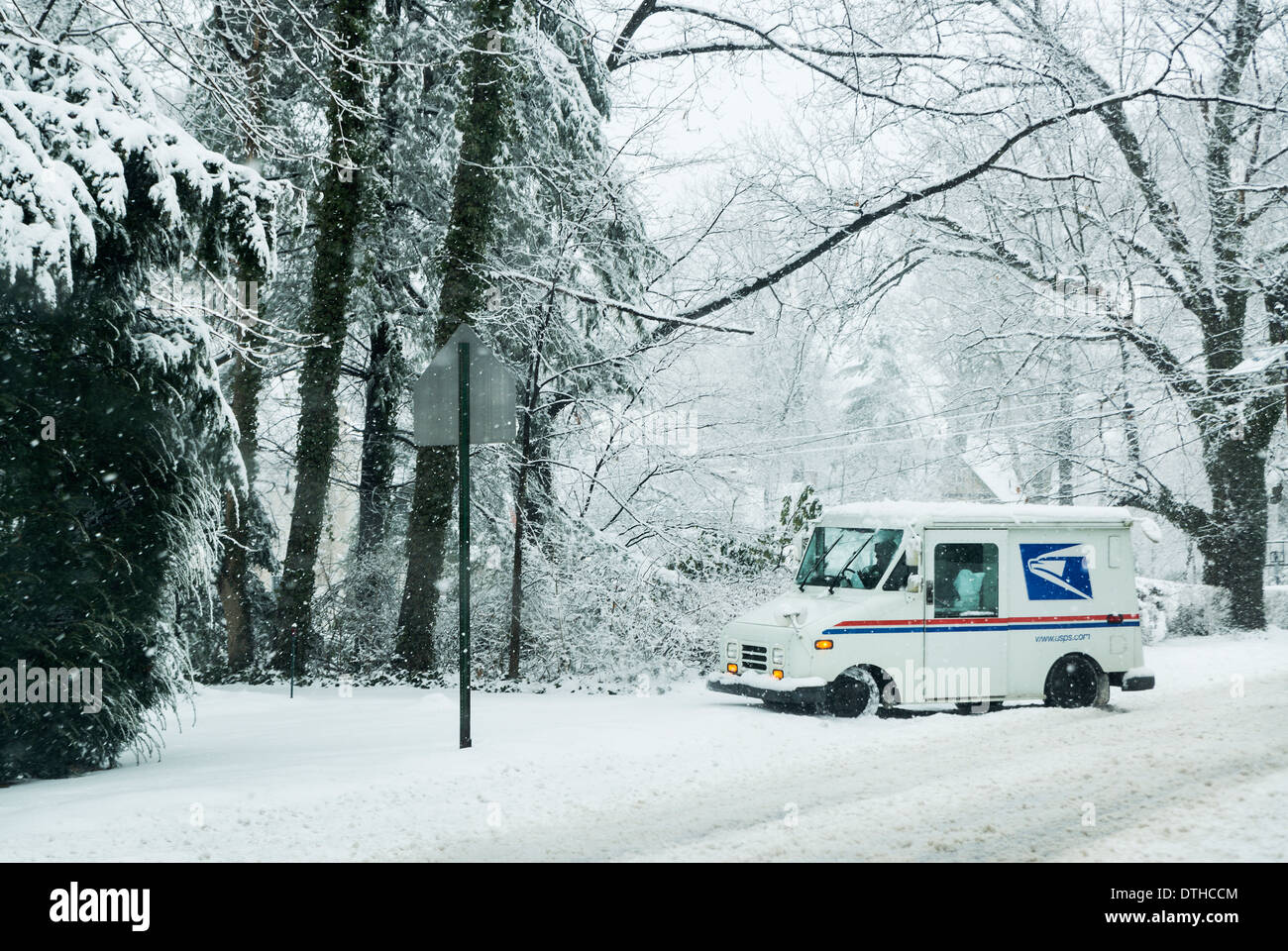 Mail delivery truck during a winter snow storm. - Stock Image
