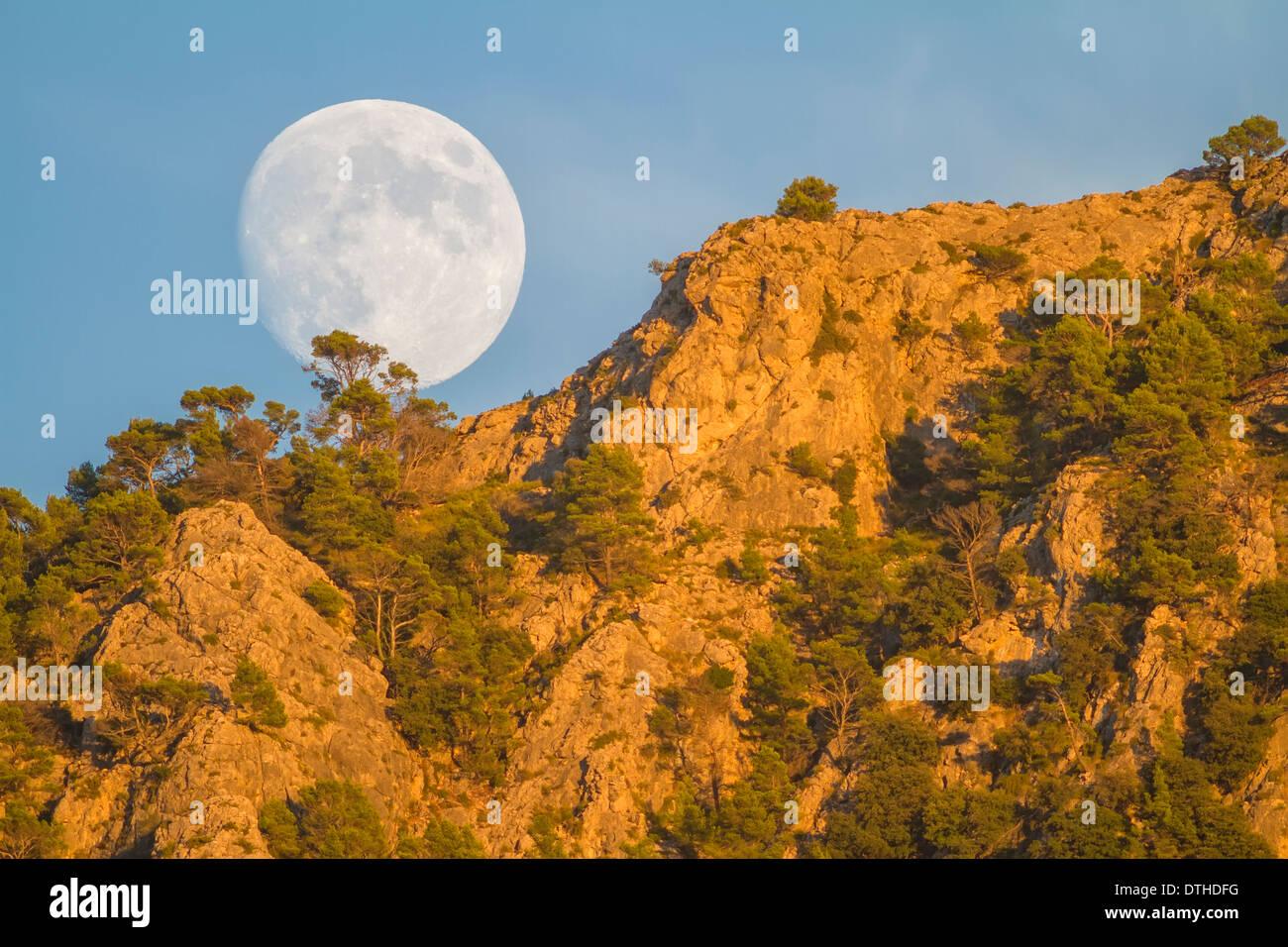 Real full moon rising over Puig des Teix mountain at sunset. Tramuntana mountains, Deià, Majorca, Balearic islands, Spain Stock Photo