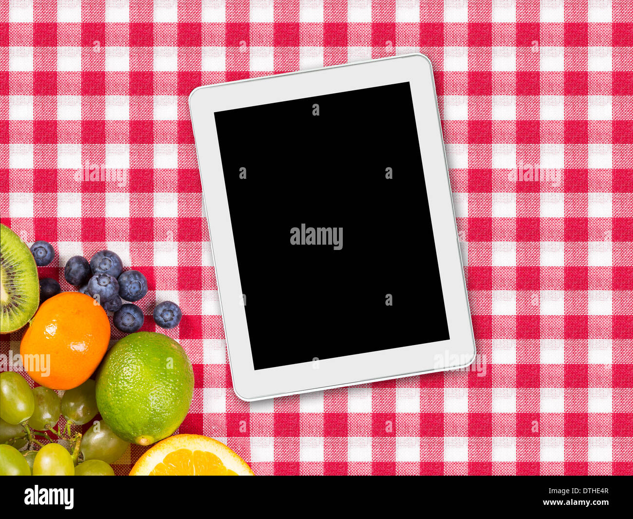 tablet and fruit on tablecloth textile - Stock Image