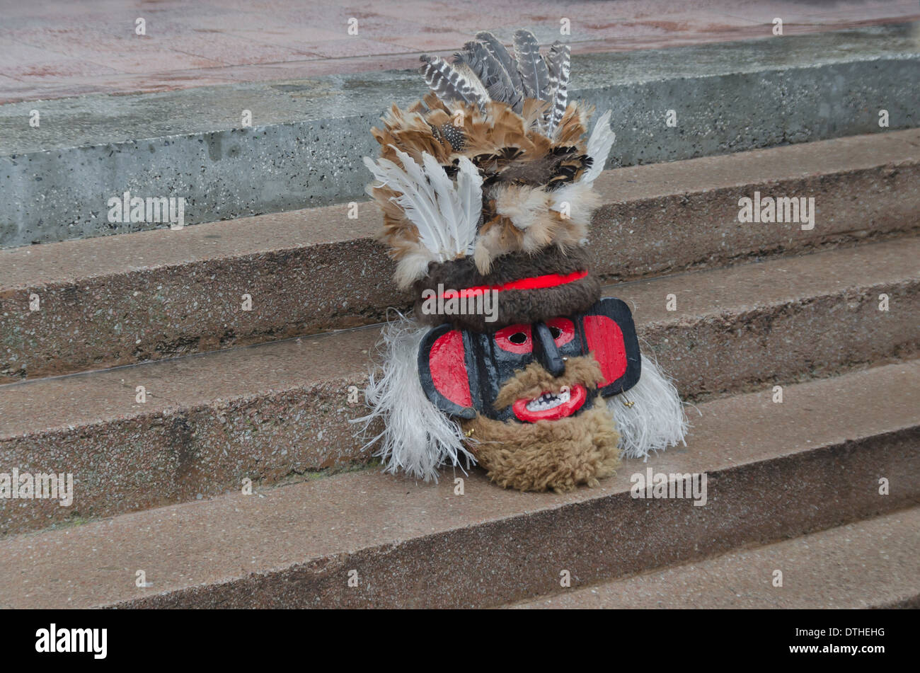 Colorful theatrical mask of mummer sitting on the staircase - Stock Image