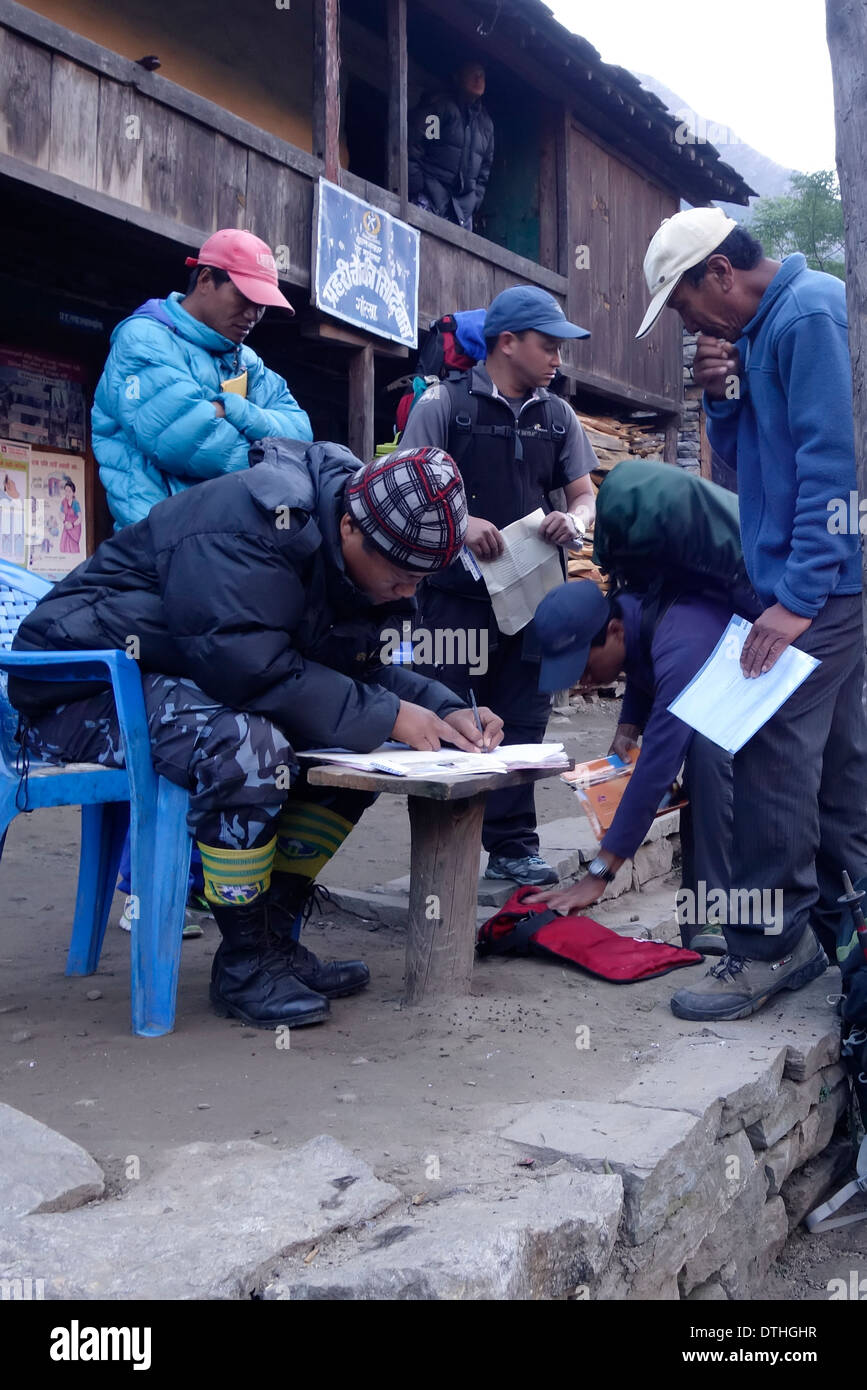 Trekking guides checking in at a checkpoint in the village of Philim on the Manaslu trekking route, Nepal. - Stock Image