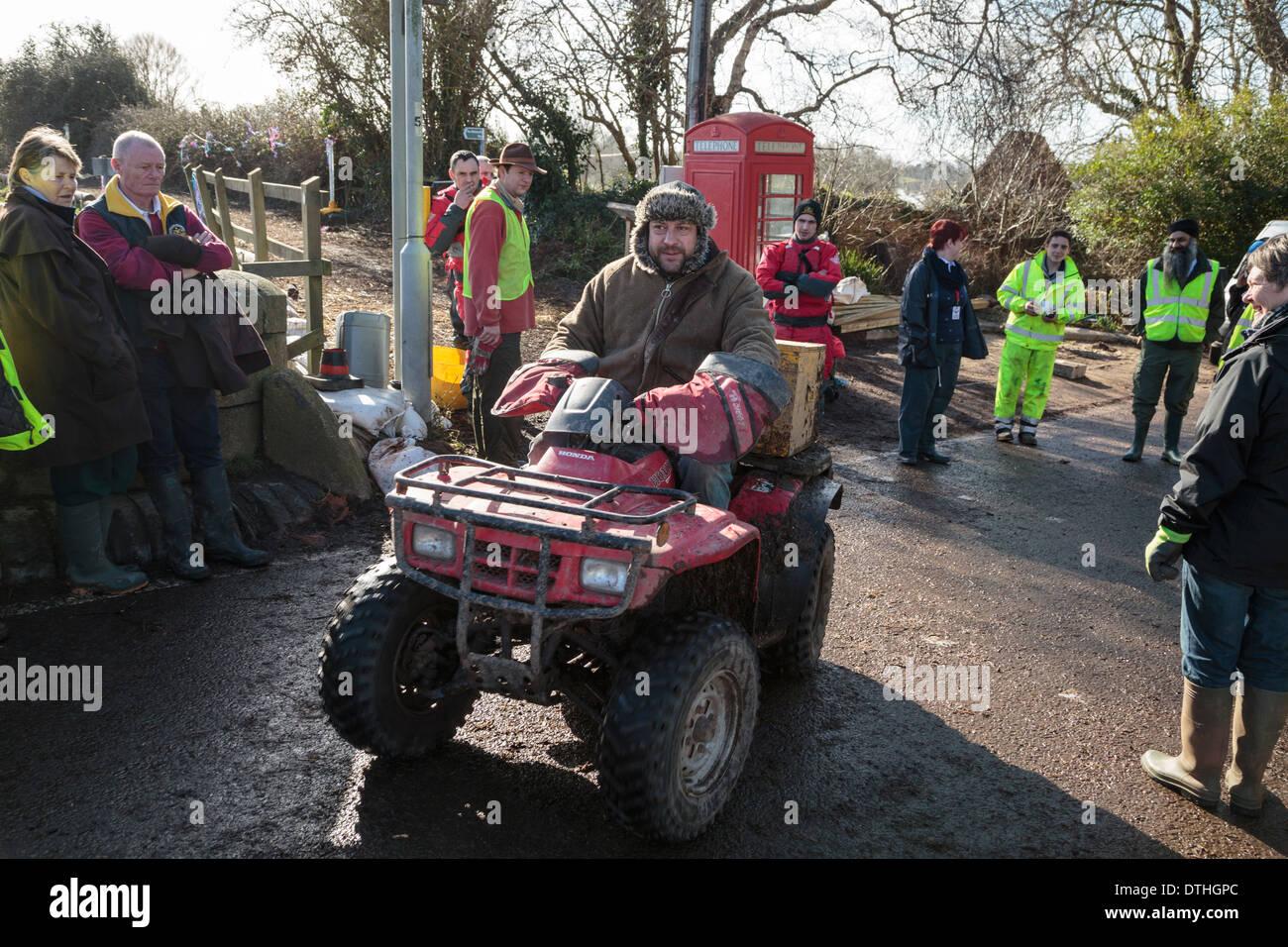 Pub landlord Jim Winkworth of the King Alfred Inn runs errands on his quad bike to help local flood victims at Burrowbridge. - Stock Image