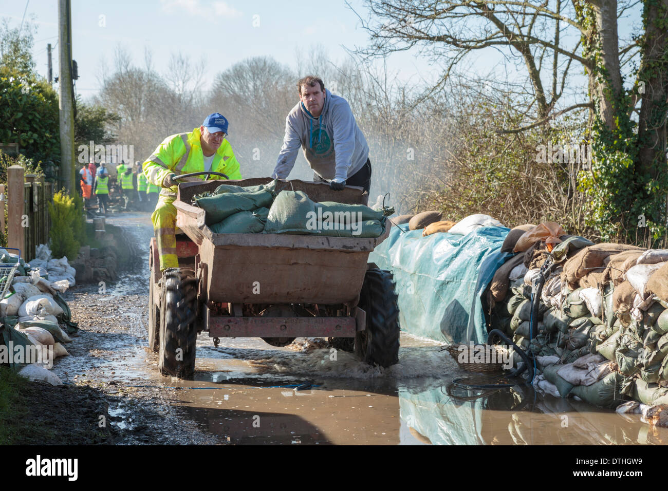 Volunteer aid workers help distribute sandbags in the flooded village of Moorland on the Somerset Levels. - Stock Image