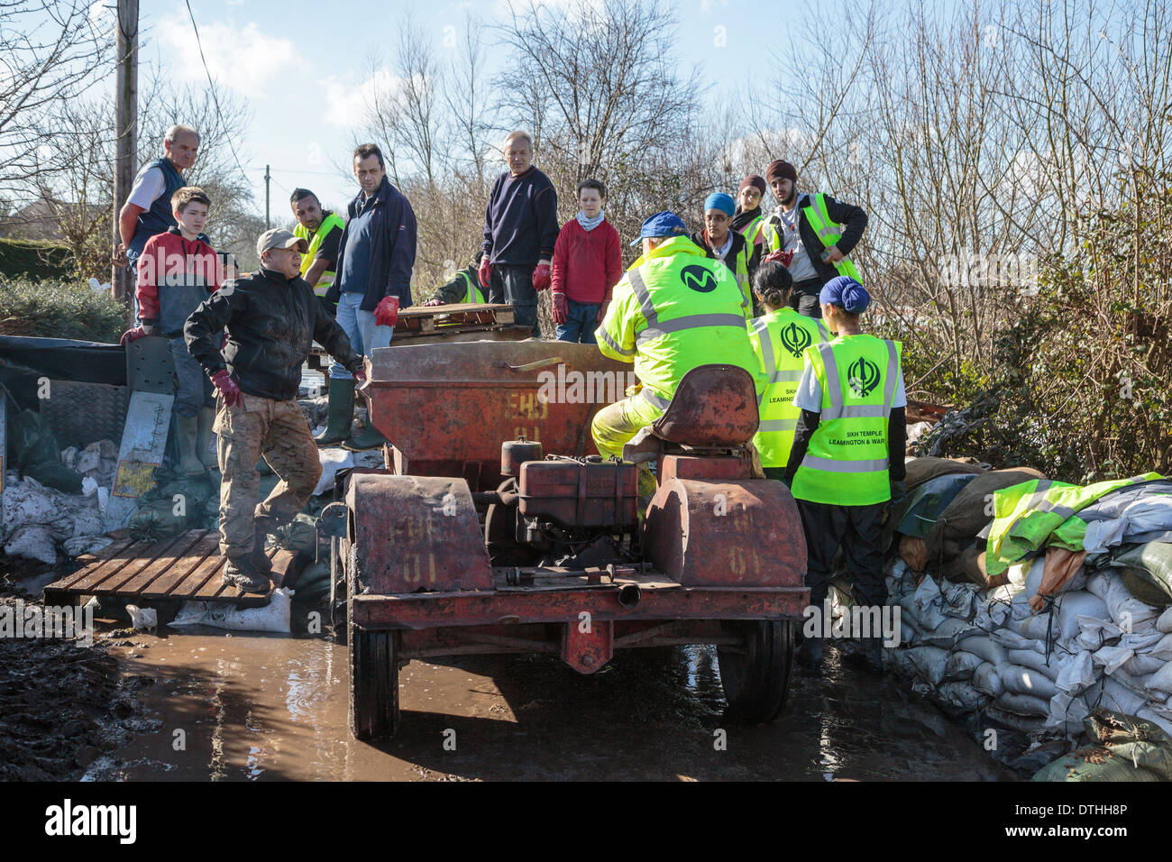 Volunteers from Khalsa Aid help distribute supplies in the flooded village of Moorland on the Somerset Levels. - Stock Image